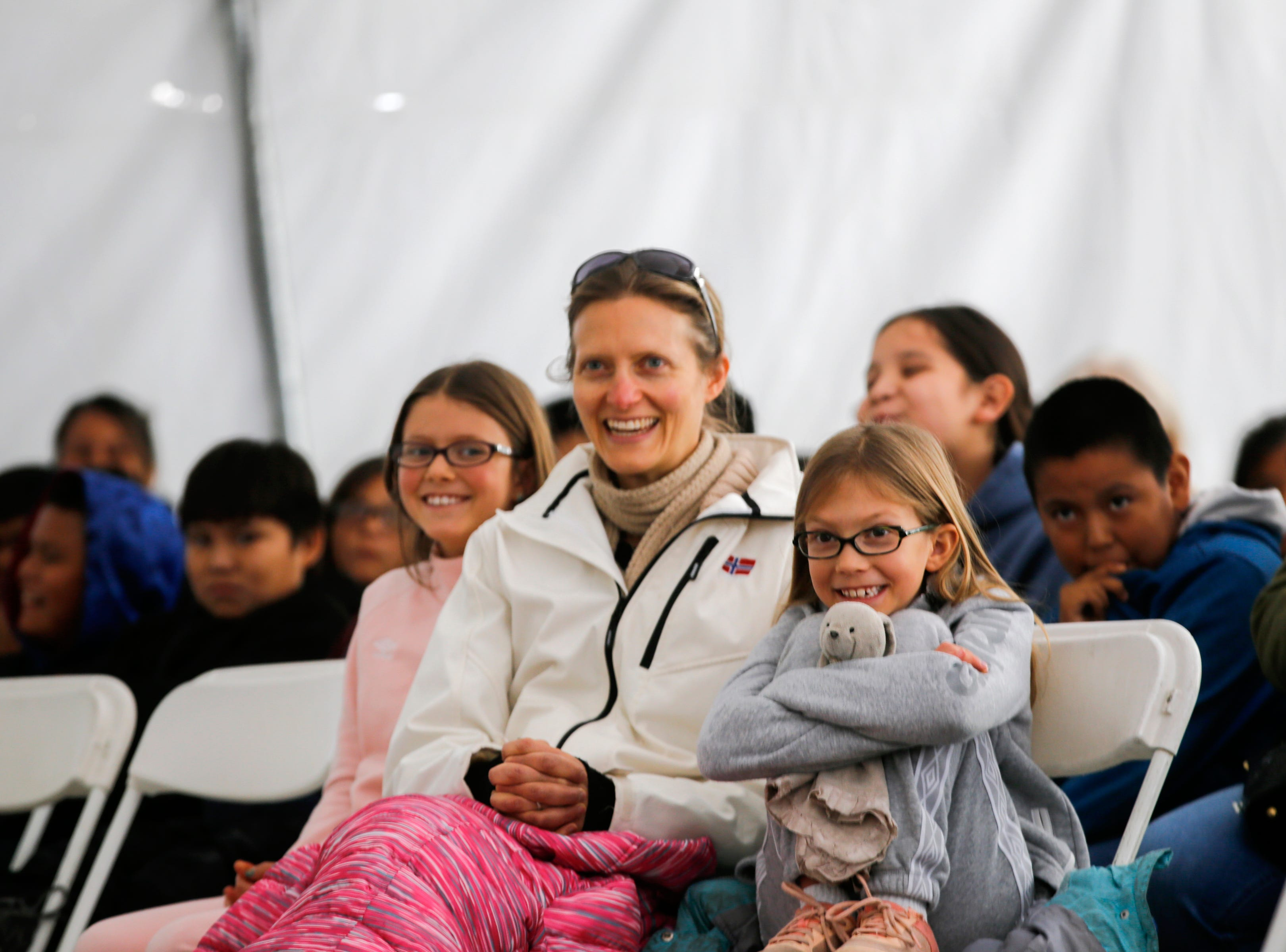 At center, Carolyn McGuire enjoys the Four Corners Storytelling Festival with her daughters, Elizabeth Seitz, left, and Abigail Seitz, right, enjoy a story with their mother Friday, Oct. 12, 2018 at Berg Park in Farmington.