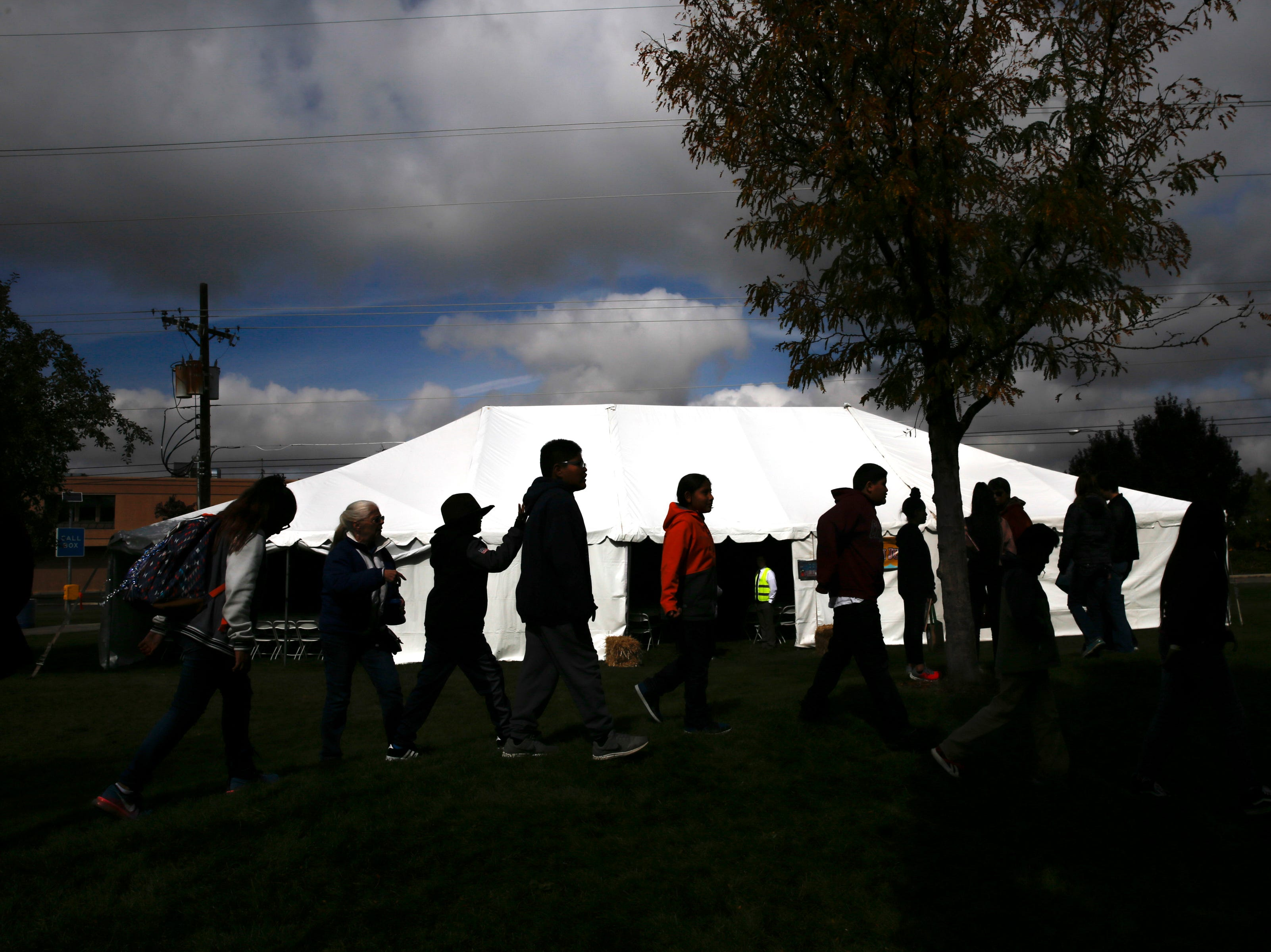 Local school children head to their next tent for more stories, Friday, Oct. 12, 2018 during the Four Corners Storytelling Festival at Berg Park in Farmington.