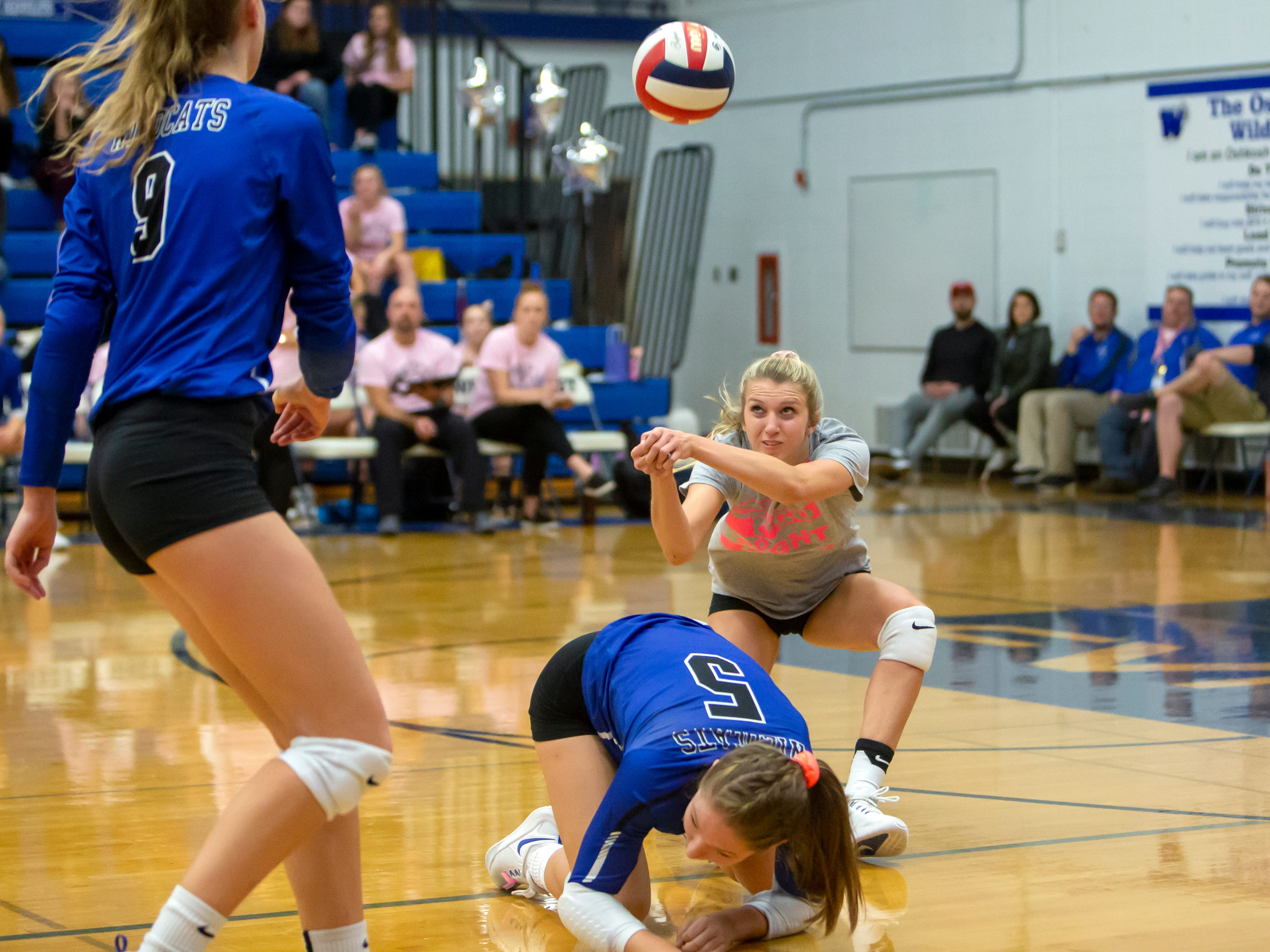 Oshkosh West's Callista Rochon-Baker dives for a bump with Rachel Mueller clearing the shot playing at Oshkosh West High School on Thursday, October 11, 2018.