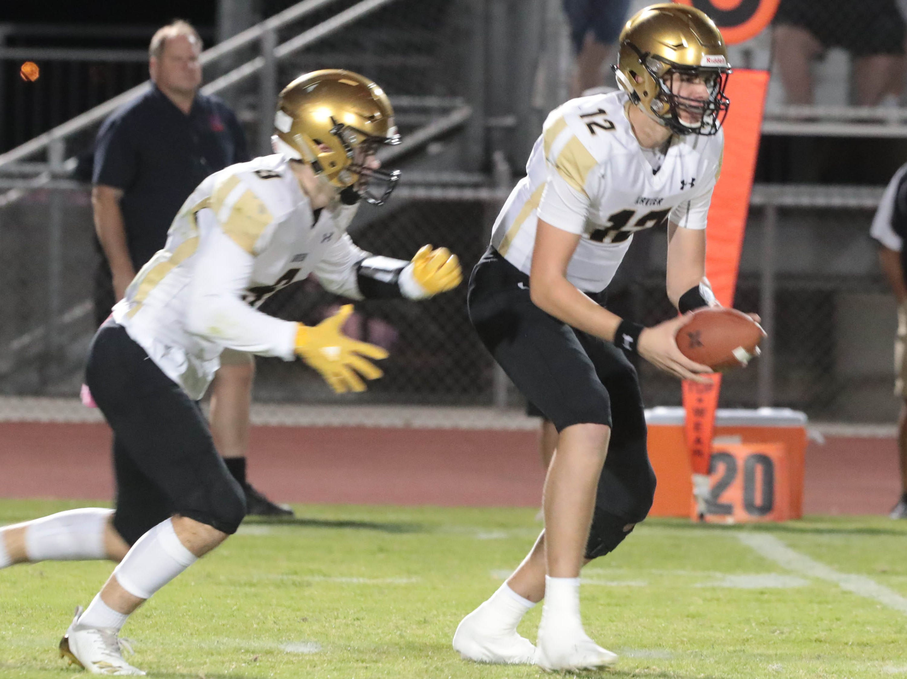 Xavier Prep quarterback Brad Mcclure hands off to Fabrice Voyne against Shadow Hills on Thursday, October 11, 2018 in Indio.