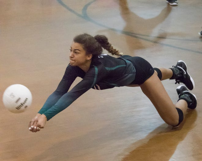 Crusader freshman Amiah Butler (11) dives for the ball during the Gulf Breeze vs Catholic volleyball match at Pensacola Catholic High School on Thursday, October 11, 2018.