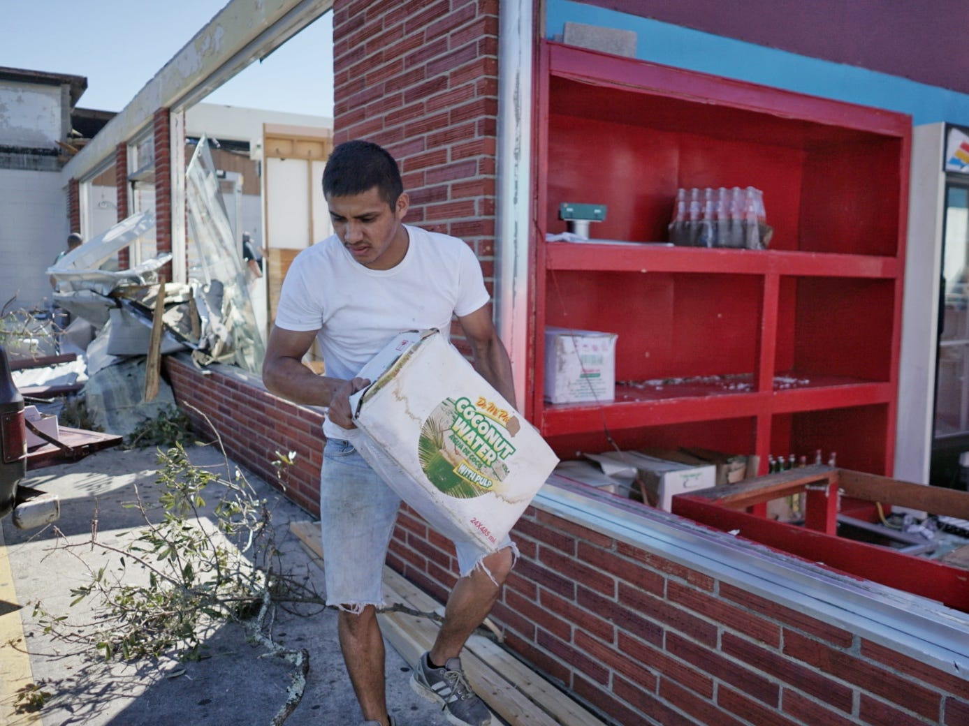 Victor Sanchez helps remove items from what's left of the family's business on in in Mexico Beach, Fla. Oct. 12, 2018.