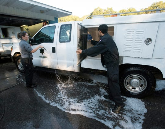 Escambia County Animal Control Officers, Sgt. Lucy Samford and Zach Fenton prepare the county vehicles for a relief mission to hurricane-ravaged Bay County on Friday, Oct. 12, 2018. Escambia County is head to the Panama City area to pick up aminals in the Bay County animal shelter. The move will clear space the storm-stricken area's pet shelter for ones displaced by the devastation.
