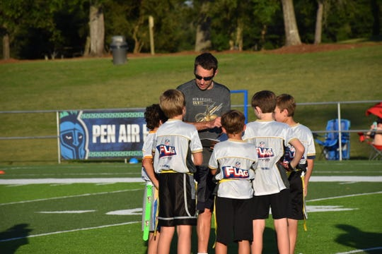 Pensacola Saints coach Charlie Penrod gathers his players for a play during practice at UWF's Pen Air Field in preparation for the NFL Flag Regional Tournament in New Orleans.