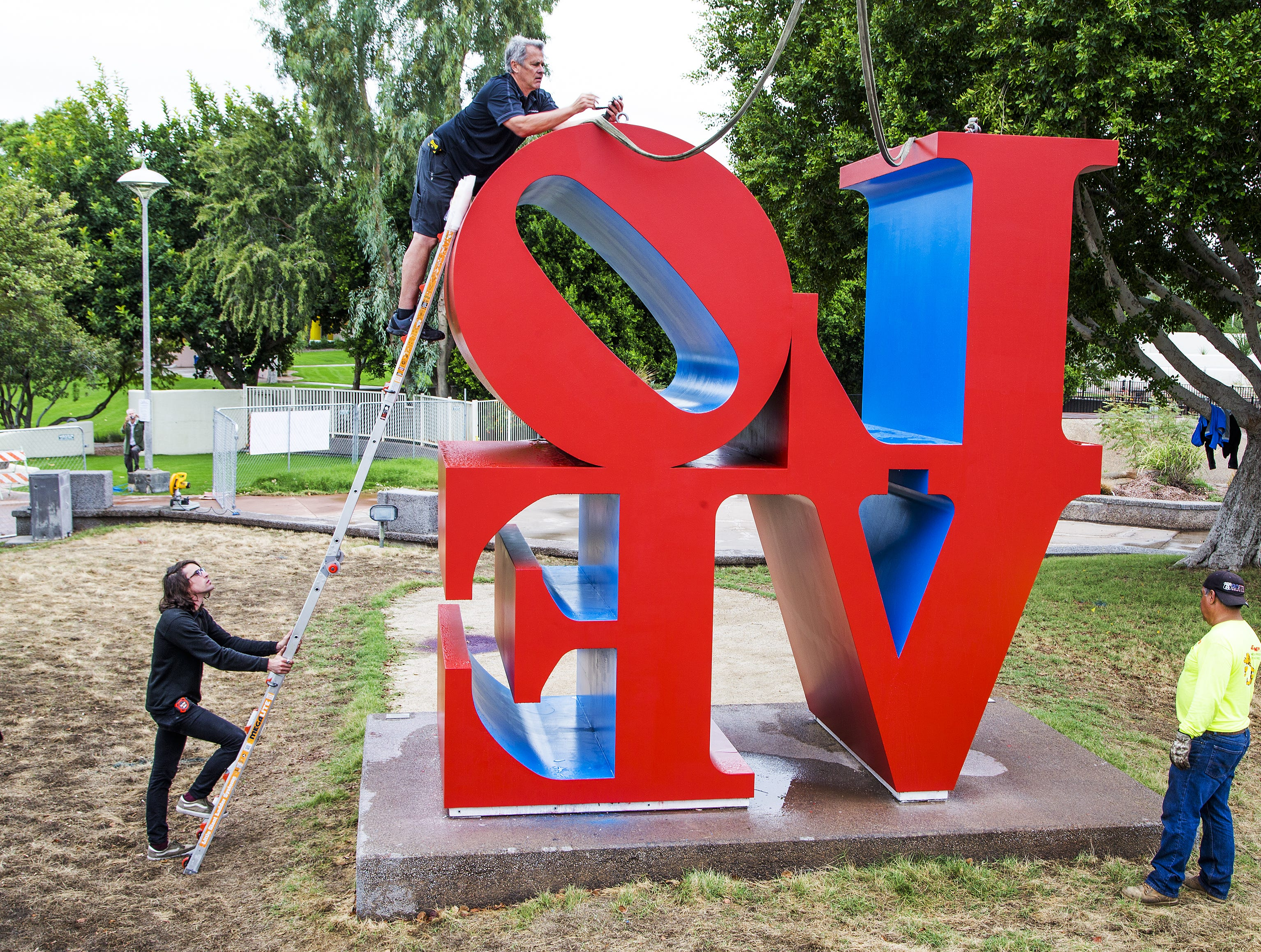 "Workers attach cables to the ""LOVE"" sculpture in front of the Scottsdale Center for the Arts on Oct.12, 2018.  A giant crane would move the sculpture about 130 feet east."