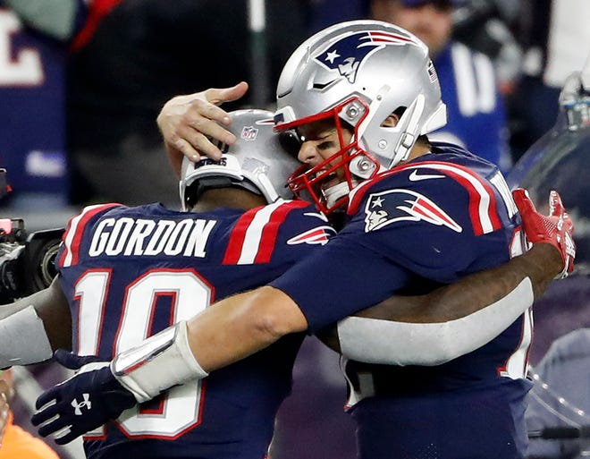 New England Patriots quarterback Tom Brady (12) hugs wide receiver Josh Gordon (10) after he caught a touchdown pass against the Indianapolis Colts during the fourth quarter at Gillette Stadium.