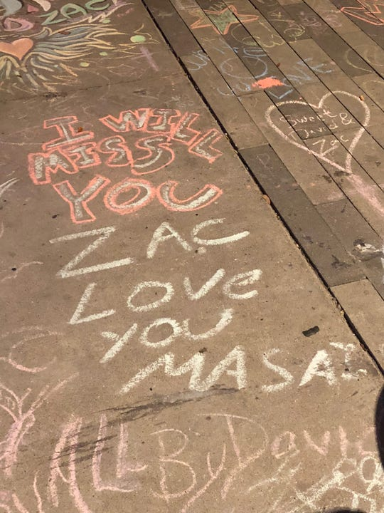 Mourners leave messages in chalk outside Jobot Coffee and Bar on Roosevelt Row in Phoenix after two employees were shot and killed on Oct. 5, 2018.