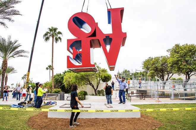 """A giant crane moves the """"LOVE"""" sculpture to its new location in front of the Scottsdale Center for the Art on Oct. 12, 2018.  The new spot is about 130 feet east of the original location."""