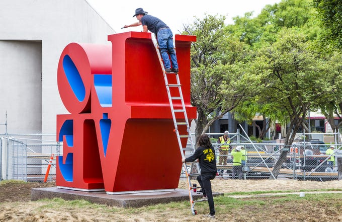 "Workers prepare to attach cables to the ""LOVE"" sculpture in front of the Scottsdale Center for the Arts on Oct. 12, 2018.  A giant crane would move the sculpture about 130 feet east."