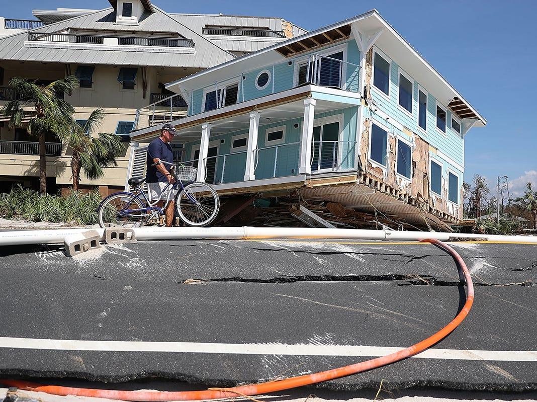 Tom Bailey pasa su bicicleta por una casa que fue transportada a través de una carretera y se estrelló contra un complejo de condominios cuando el huracán Michael pasó por el área el 11 de octubre de 2018 en Mexico Beach, Florida. El huracán golpeó con vientos de categoría 4 que causaron daños mayores.