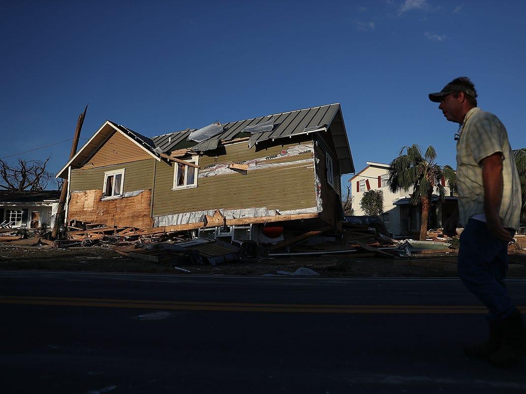 Una persona pasa frente a una casa que fue derribada cuando el huracán Michael pasó por el área el 11 de octubre de 2018 en Mexico Beach, Florida. El huracán golpeó con vientos de categoría 4 que causaron daños mayores.