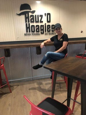 Beth Riggan, owner of Hauz O'Hoagies, poses in front of a display inside her specialty hoagie shop now open in Campbelltown.