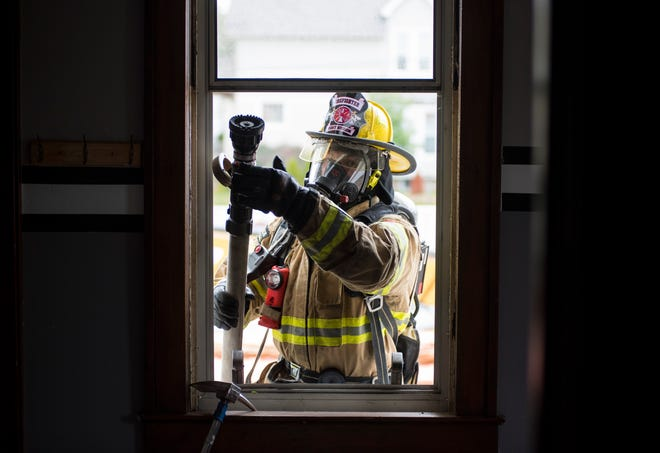 Port Huron firefighter Sean Dalton lifts a hose through a broken second-floor window during a training session Friday, Oct. 12, 2018 at a vacant house in Port Huron.