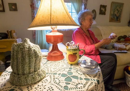 Margie Starkey sorts through a basket of yarn Thursday, Oct. 11, 2018 in the workspace of her home, where she makes hats, scarves and gloves each year to give to local charities.