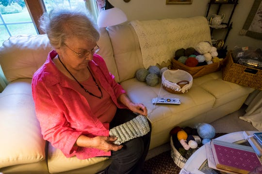 Margie Starkey looks at a headband she's making Thursday, Oct. 11, 2018 in the workspace of her home, where she makes hats, scarves and gloves each year to give to local charities.