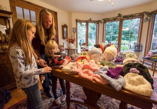 Margie Starkey's neighbors Chrstina Bass helps her daughters Elizabeth, 10, and Annabelle, 5, pick out scarves and hats Thursday, Oct. 11, 2018 in Starkey's house.