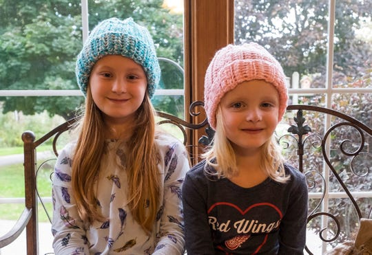 Elizabeth Bass, 10, left, and her sister Annabelle, 5, model hats made by Margie Starkey Thursday, Oct. 11, 2018 in Starkey's home.