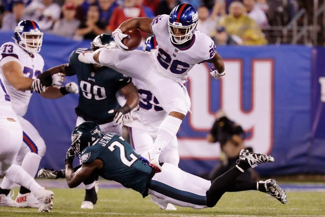 New York Giants' Saquon Barkley (26) hurdles Philadelphia Eagles' Malcolm Jenkins (27) during the first half of an NFL football game Thursday, Oct. 11, 2018, in East Rutherford, N.J. (AP Photo/Julio Cortez)