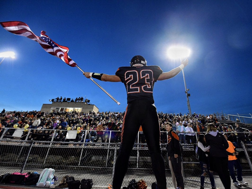 Northeastern's Kyle Williams waves the American flag in front of the Bobcats' student section prior to the start of Friday's game against Central York.