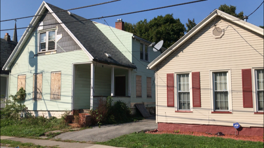"Ibero's ""crack house"" (left) next to the Alston family's tidy home on Hoeltzer Street."