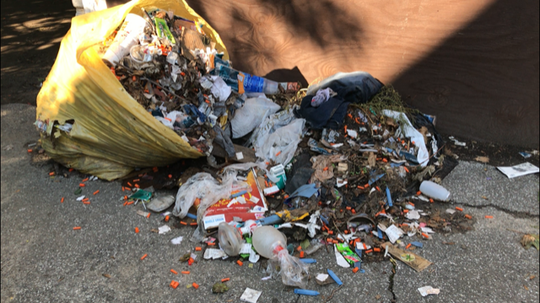 Bags of trash filled with syringes and drug paraphernalia litter the grounds at 20 Hoeltzer Street.