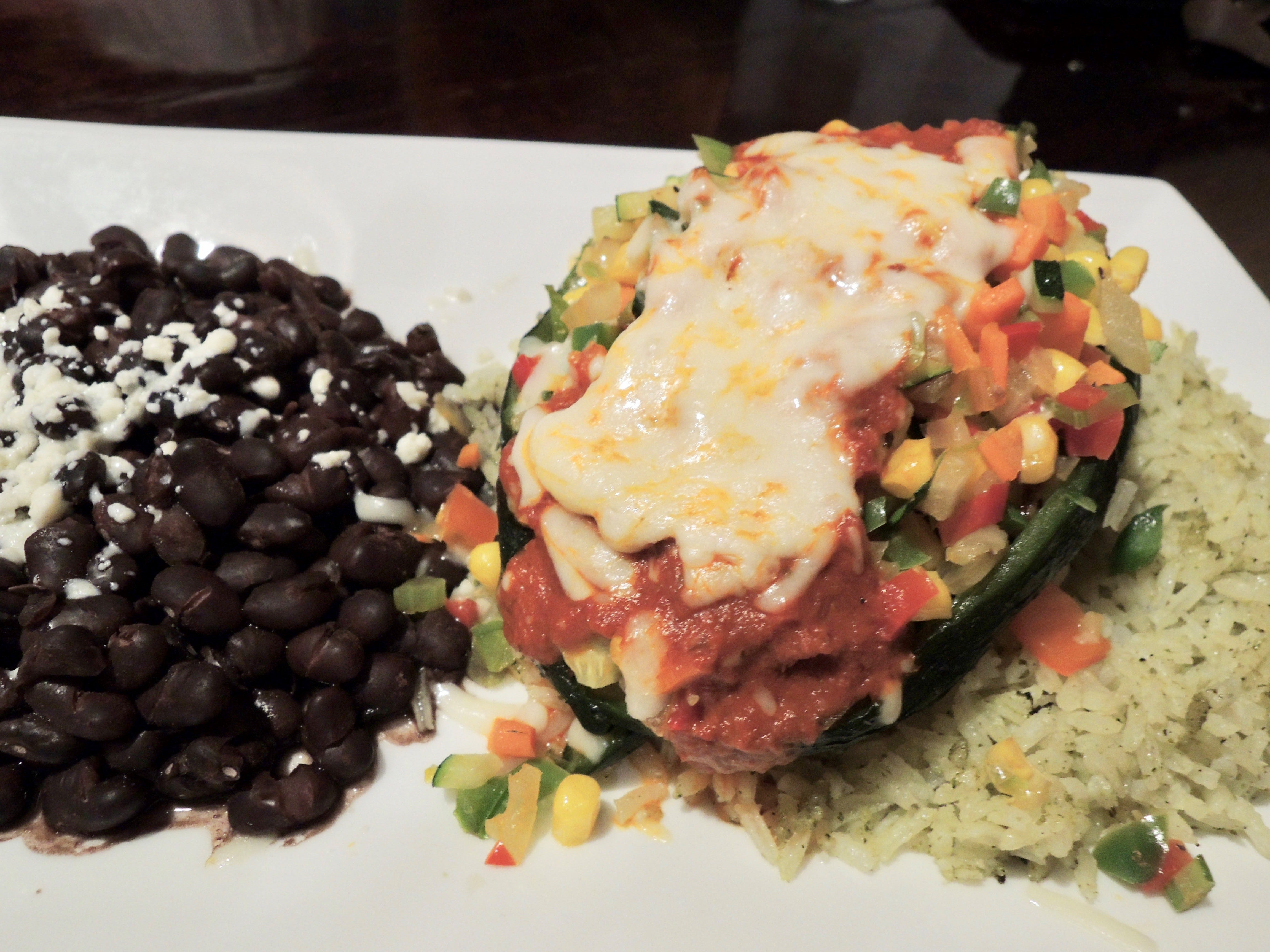A veggie relleno in a roasted poblano pepper served with green rice and black beans at Cicada Cantina.