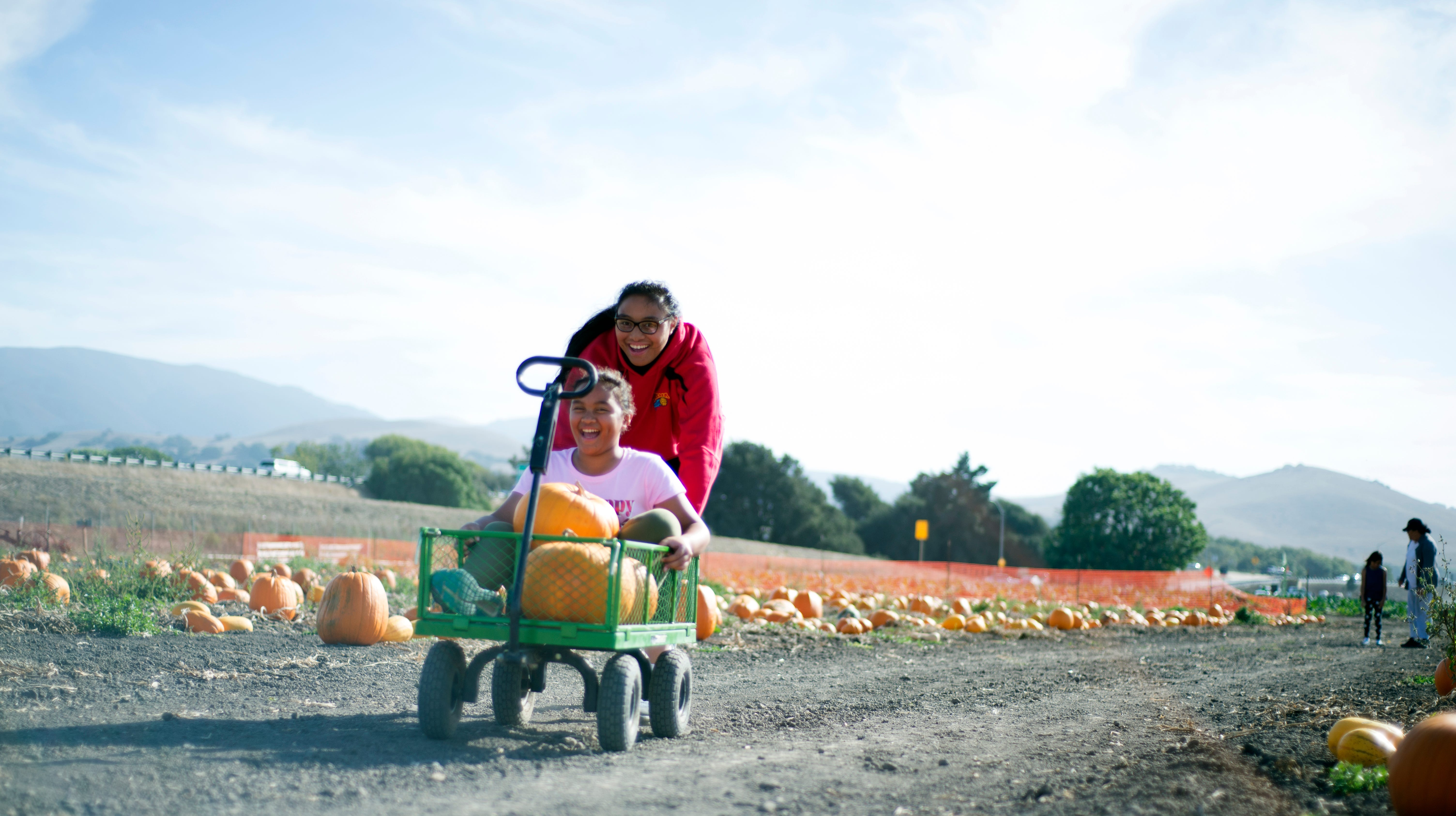 Alexis Jimenez, 16, pushes Maribeth Jimenez, 10, in a wagon between rows of pumpkins at The Farm in Salinas on Oct. 9, 2018.
