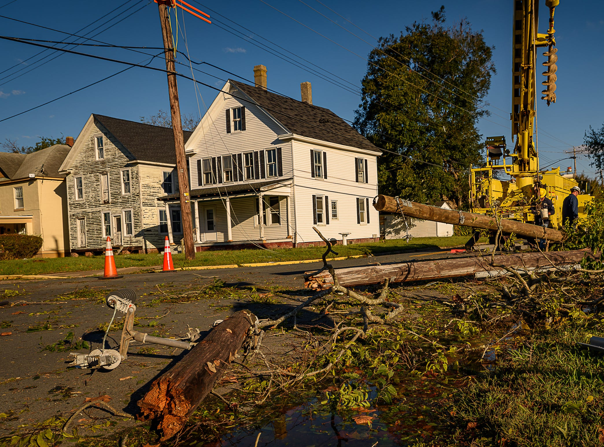 With the broken remains of a damaged utility pole in the street in Cape Charles, ANEC works to replace it.