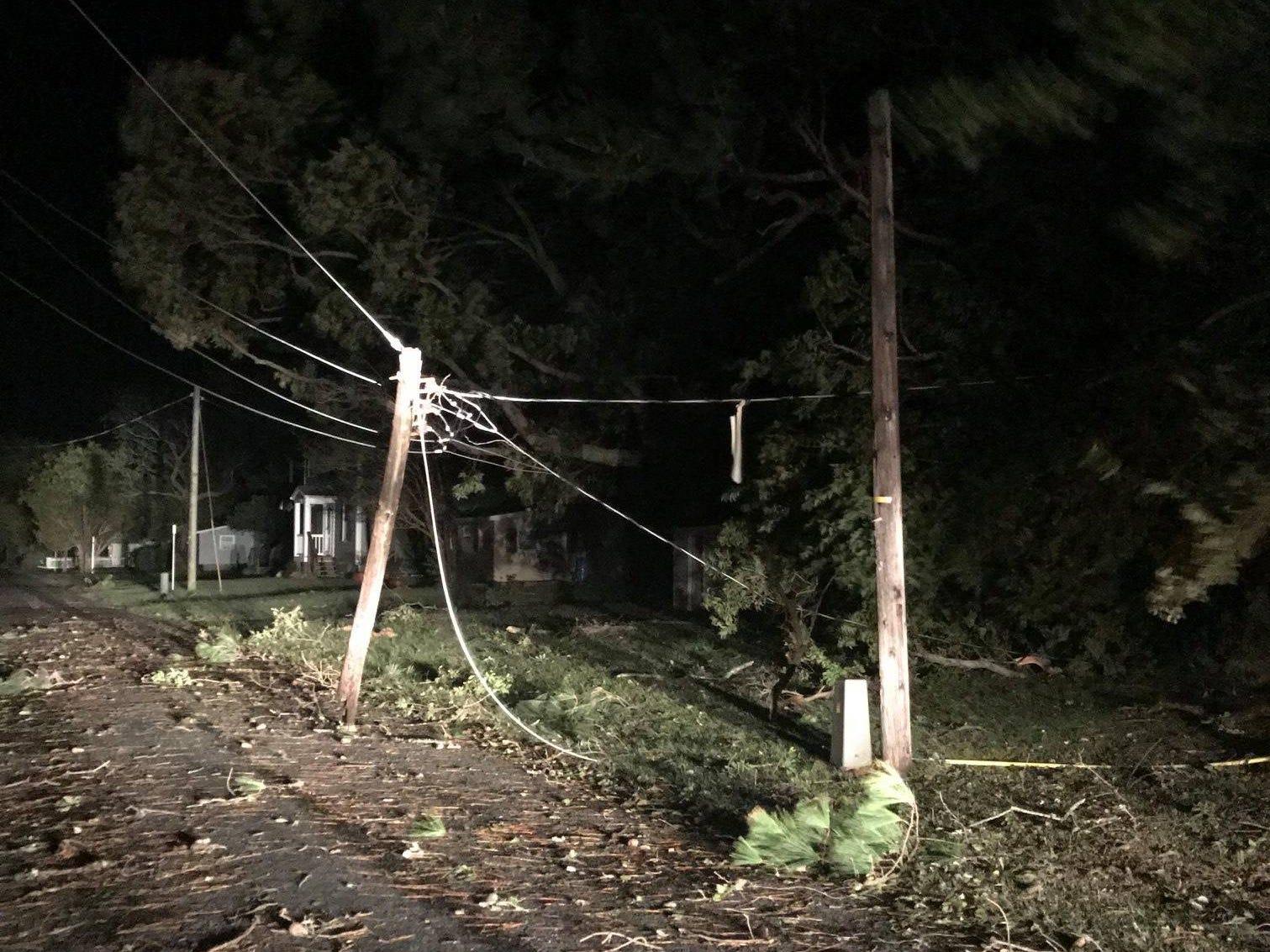 A broken utility pole blocks the road at Smith Beach, near Eastville, Virginia.