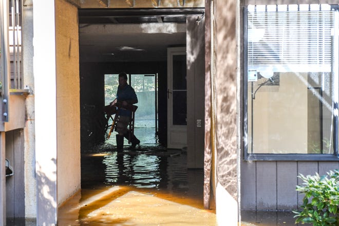 Residents evacuate flooded Canal Woods apartments on Friday, Oct 12, 2018 after Tropical Storm Michael passed through Salisbury overnight.