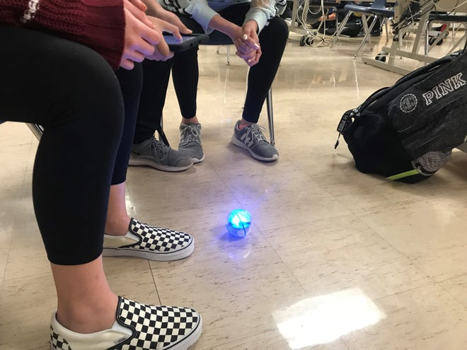 In a STEM class, students work on a tablet to move a sphere via the computer program.