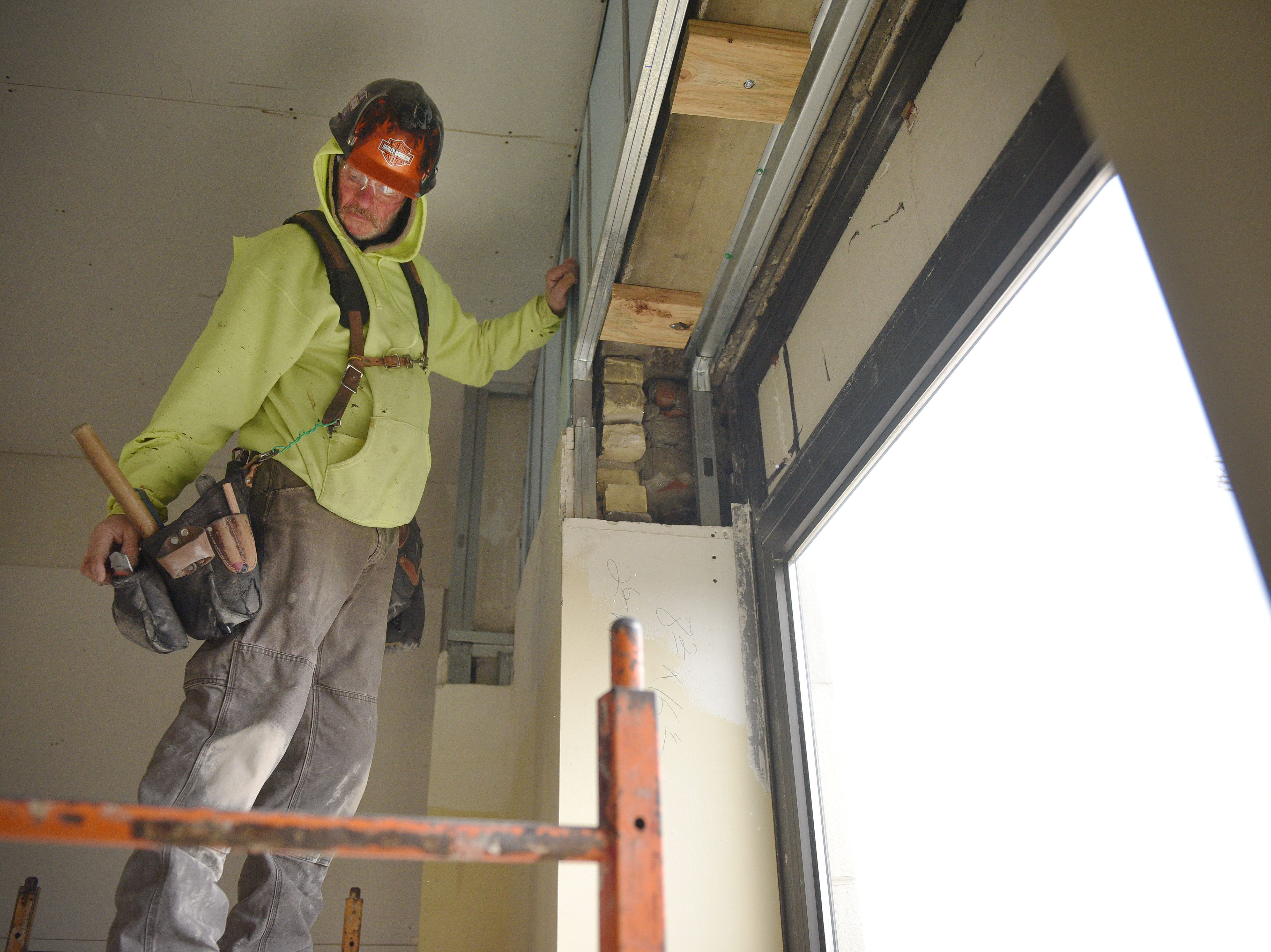 Fox Drywall & Plastering worker Jerald Swift works on insulating the exterior frame with foam in Hotel Phillips Thursday, Oct. 11, in downtown Sioux Falls. The luxury hotel is an ongoing remodel of the old Great Western building.