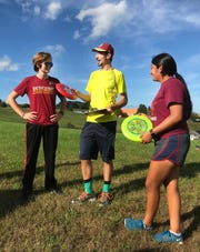 Fort Defiance Ultimate players Max Jones and Amy Cortes take pointers from Coach Josh Bollinger.