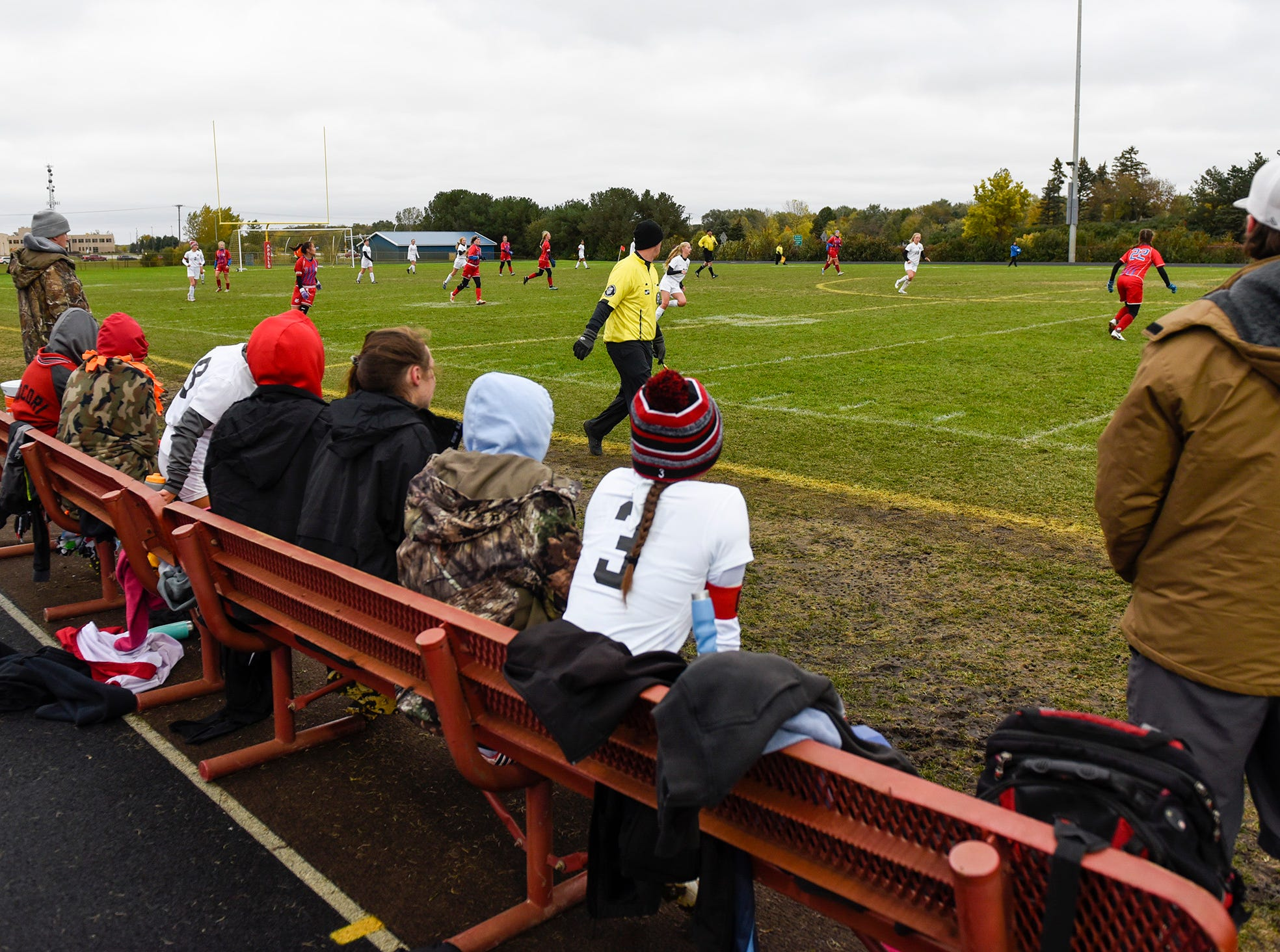 Players watch the game from the bench during the first half Thursday, Oct. 11, at Apollo High School.