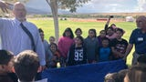 Mesquite Rotary President Kevin Boyer and Beaver Dam Elementary School students in Littlefield, Arizona, unveil a Buddy Bench on Oct. 10, 2018.