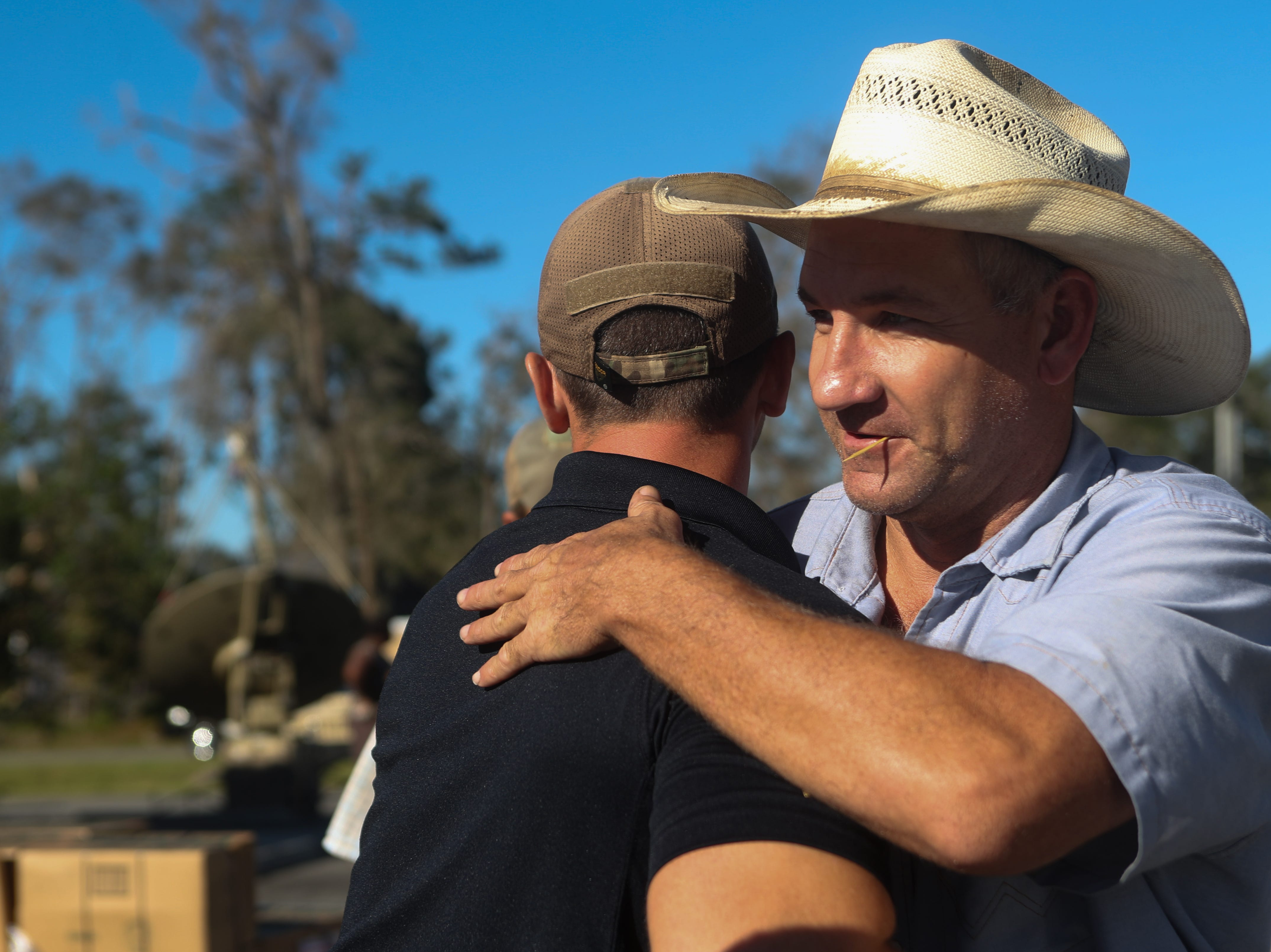 Florida Department of Law Enforcement Agent Robert Arnold, left, hugs David Carson, right, as they see each other for the first time in the aftermath of Hurricane Michael Friday, Oct. 12, 2018. Arnold was working at the Liberty County Emergency Operations Center in Bristol, Fla. to distribute food and water to residents.