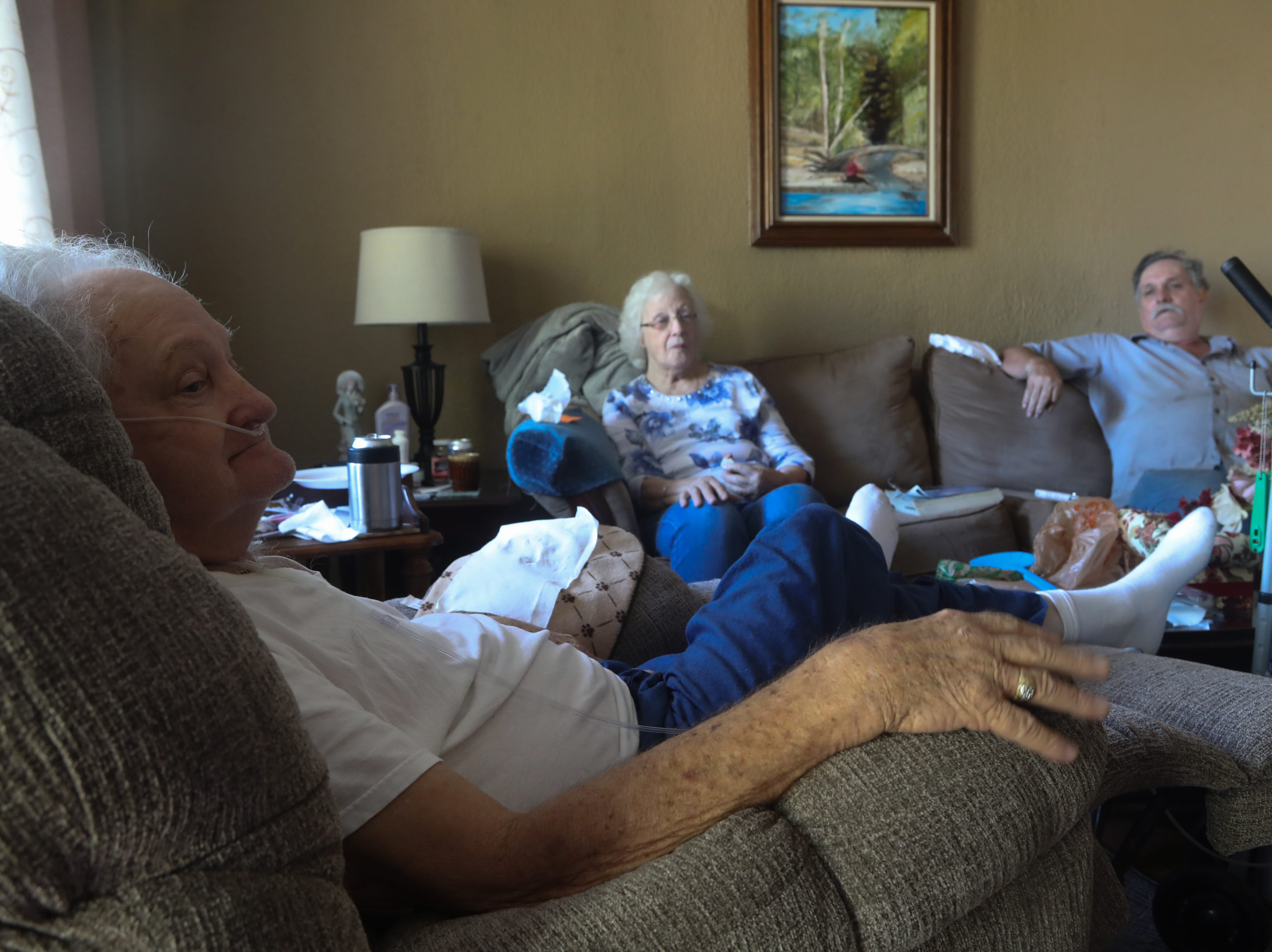 Hubert Pitts, Sue Pitts and Randal Blackburn sit in their living room while trees are down in their front yard in the aftermath of Hurricane Michael Friday, Oct. 12, 2018.