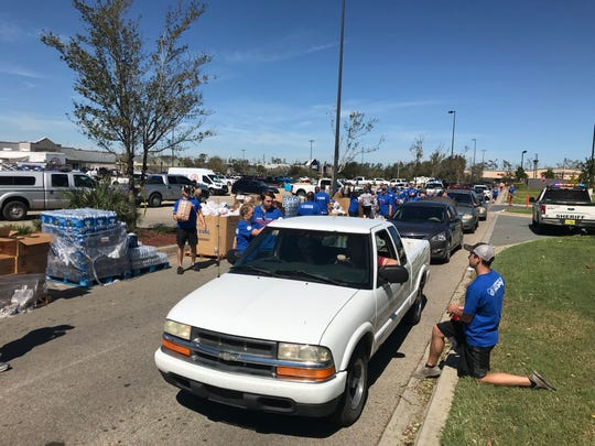 Volunteers with Convoy of Hope give out food and water Friday at the Walmart in Marianna.