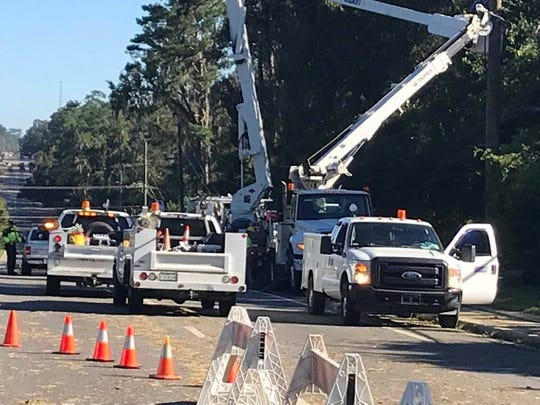 Crews from out of town work to repair extensive damage to power poles and lines along a stretch of Thomasville Road.