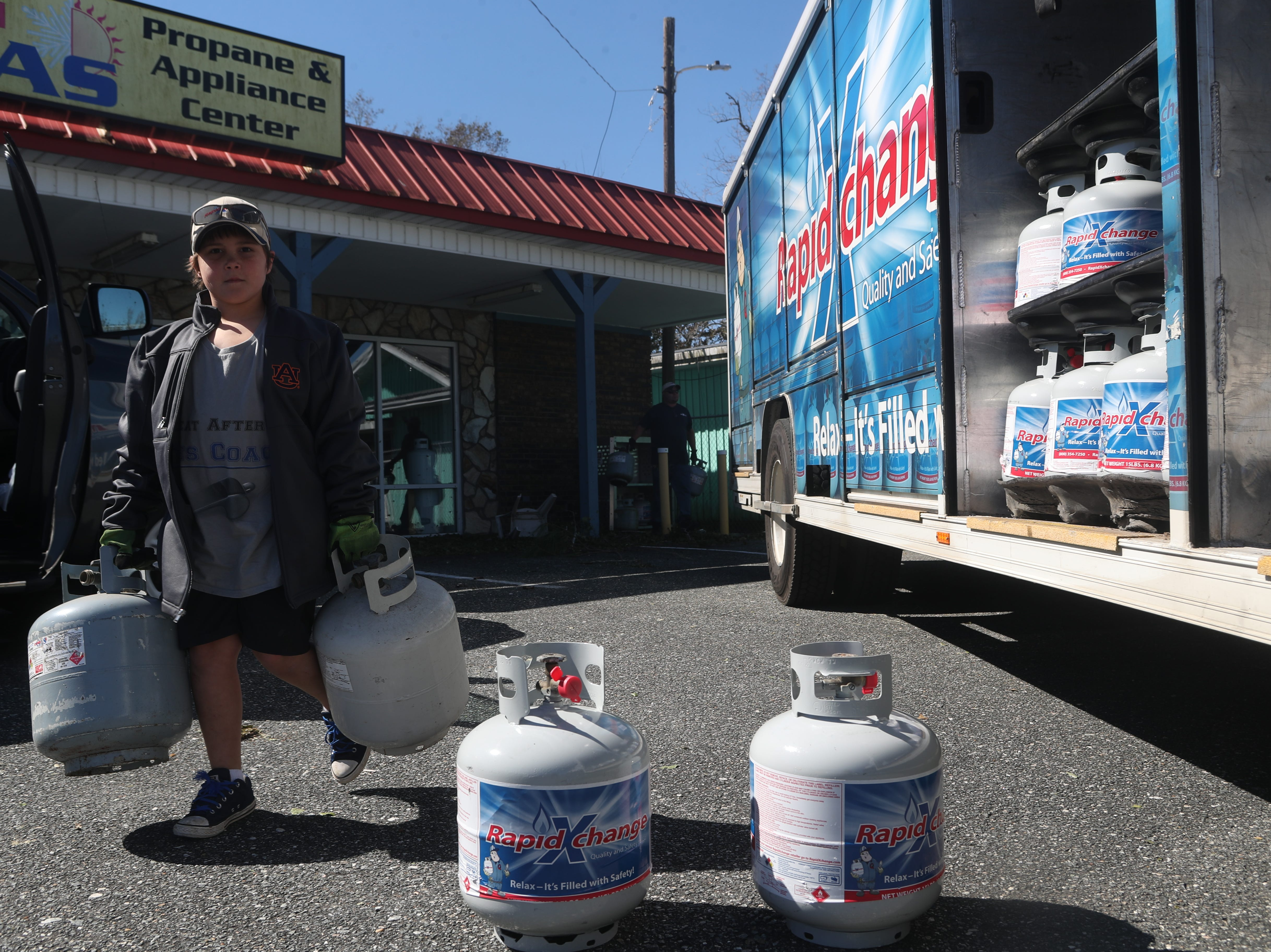Trent Killingsworth, 10, helps his dad Todd deliver propane to Blountstown, Fla. in the aftermath of Hurricane Michael Friday, Oct. 12, 2018.