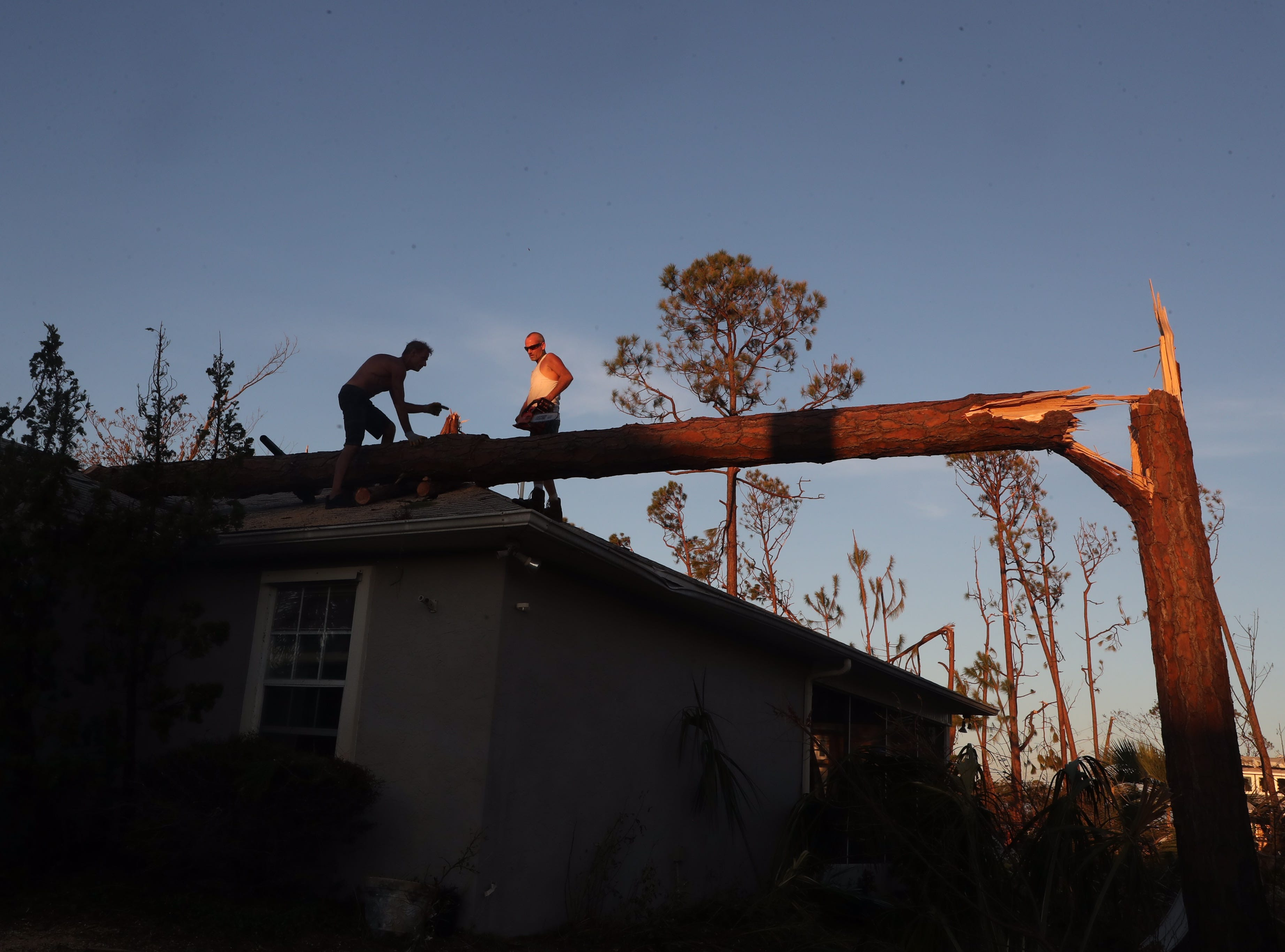 Brandon Felts, right, helps Mexico City homeowner Michael Scoggins remove a tree for the top of his home Thursday. Hurricane Michael made a direct hit on Mexico City, Fla.