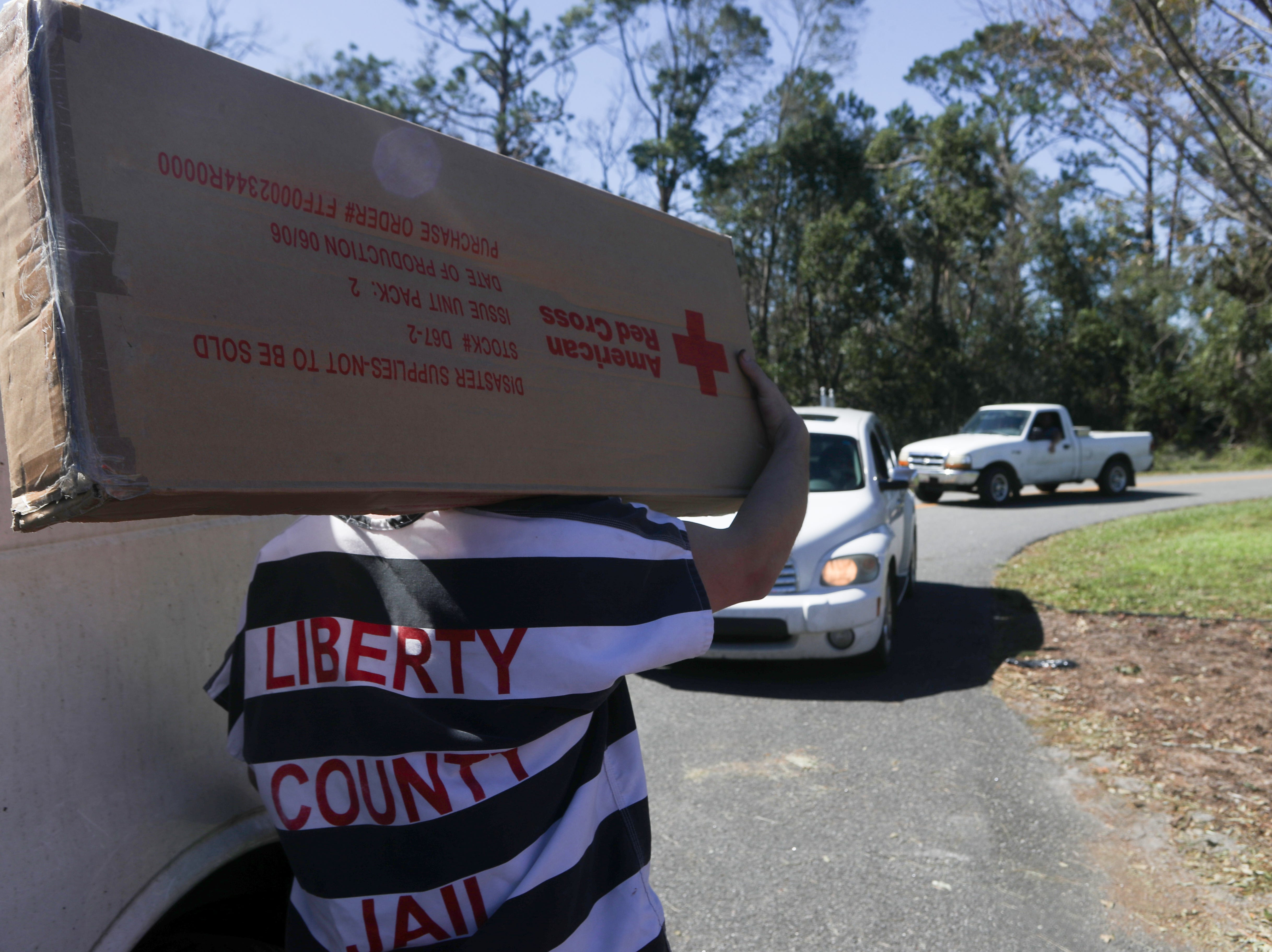 Liberty County jail inmates help distribute American Red Cross cots and blankets at the Liberty County Emergency Operations Center in Bristol, Fla. in the aftermath of Hurricane Michael Friday, Oct. 12, 2018.