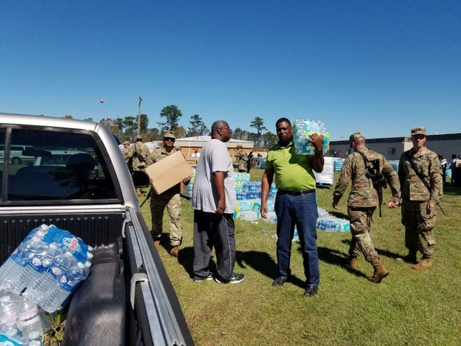 Several soldiers, volunteers and Gadsden County Sheriff Morris Young load water and supplies into a pick up truck Friday afternoon at the county jail. Scores of residents lined up for water, food and tarps following Hurricane Michael's impact Wednesday.