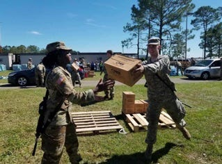 Two National Guardsmen work to load read-made meals for Quincy residents at a water and supplies distribution site at the Gadsden County Jail.