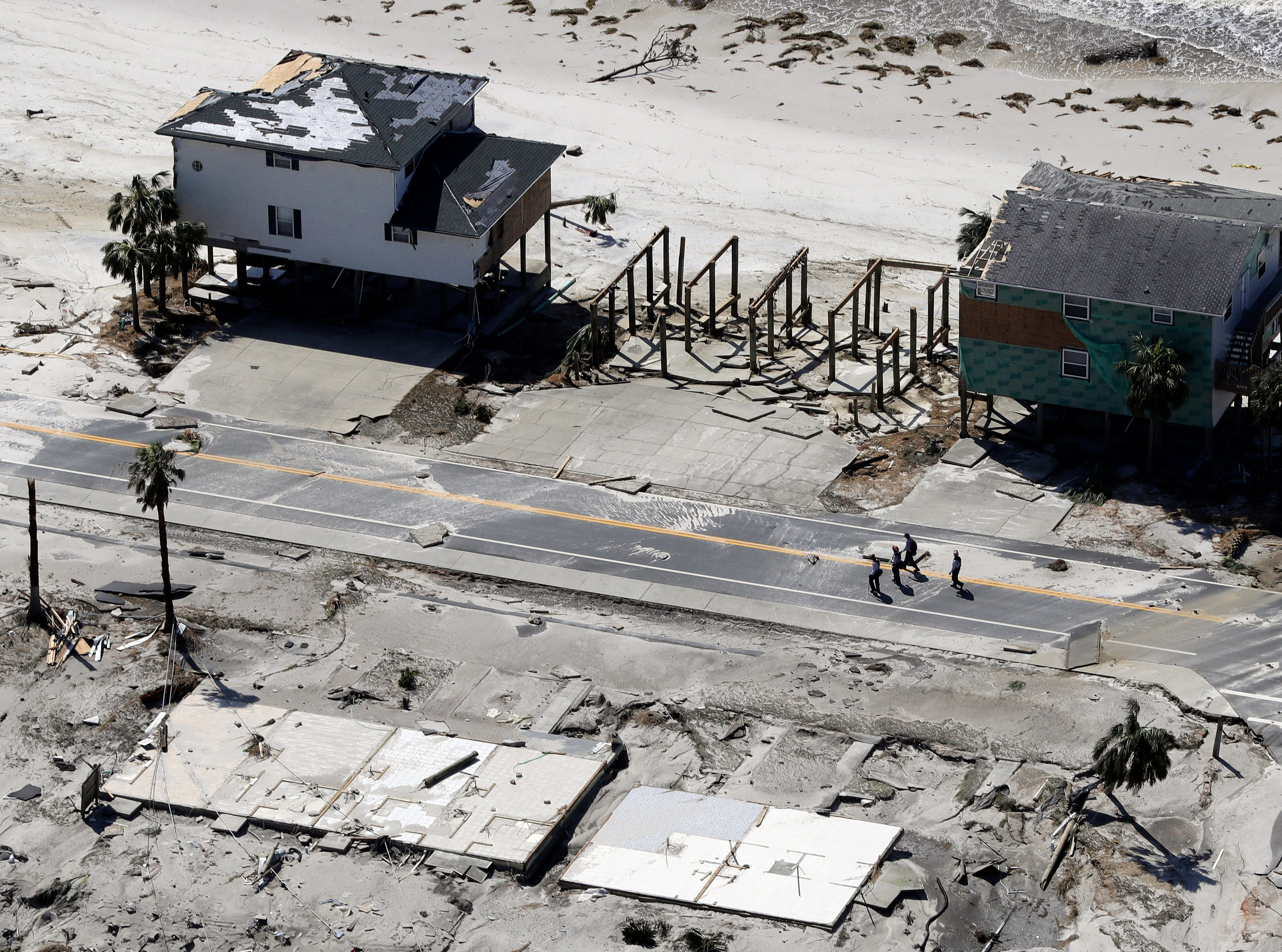 People walk past homes destroyed by Hurricane Michael are shown in this aerial photo Thursday, Oct. 11, 2018, in Mexico Beach, Fla. The devastation inflicted by Hurricane Michael came into focus Thursday with rows upon rows of homes found smashed to pieces, and rescue crews began making their way into the stricken areas in hopes of accounting for hundreds of people who may have stayed behind. (AP Photo/Chris O'Meara)