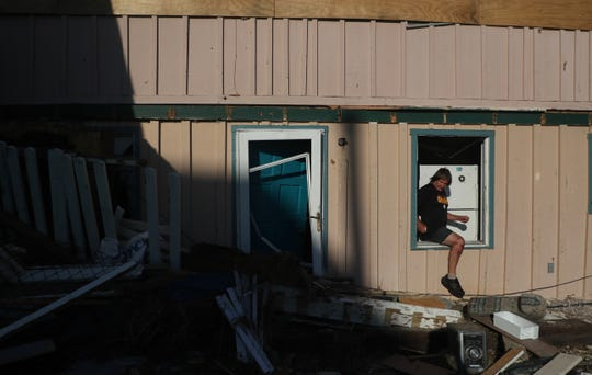 James Murphy crawls out of his Beacon Hill home on Thursday. It was destroyed in Hurricane Michael. It was at ground zero for the hurricane.
