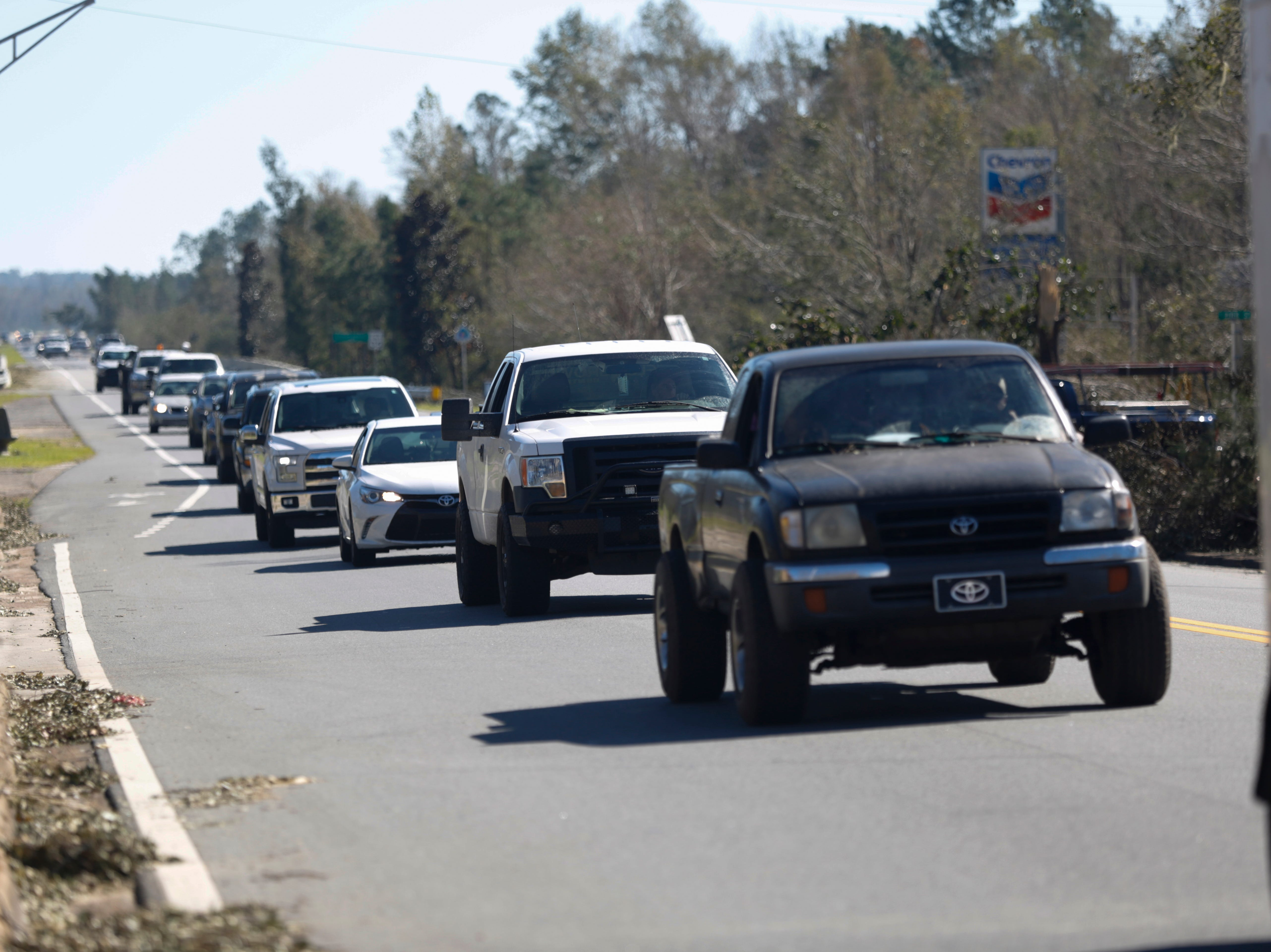 Miles of cars drive into Blountstown via Highway 20 in Blountstown, Fla. in the aftermath of Hurricane Michael Friday, Oct. 12, 2018.