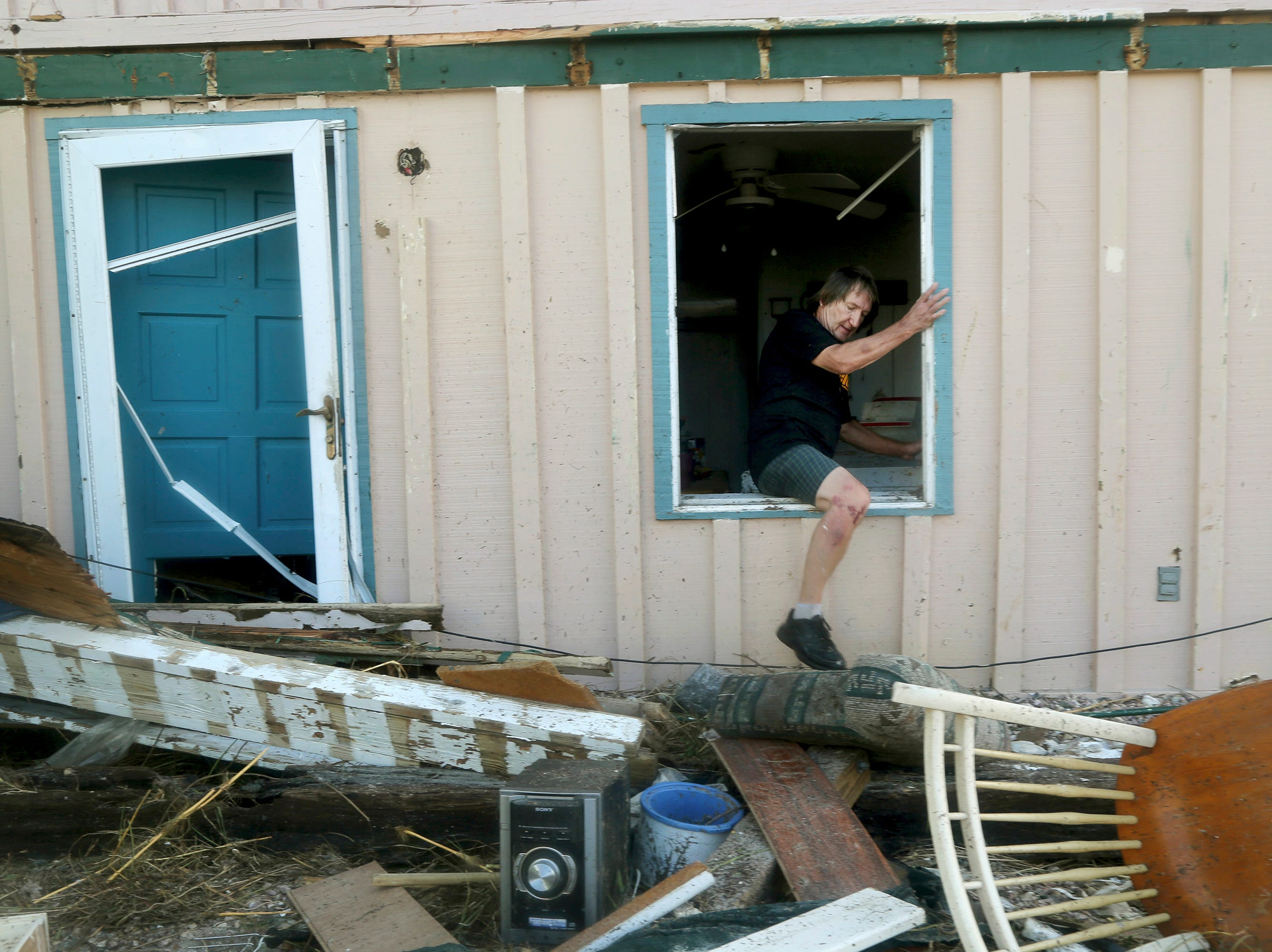 James Murphy emerges from what remains of his home on Thursday, Oct. 11, 2018, on a coastal stretch of Port St. Joe, Fla. The home was severely damaged by Hurricane Michael's violent storm surge and wind as it made landfall on Wednesday in the Florida Panhandle. (Douglas R. Clifford/Tampa Bay Times via AP)