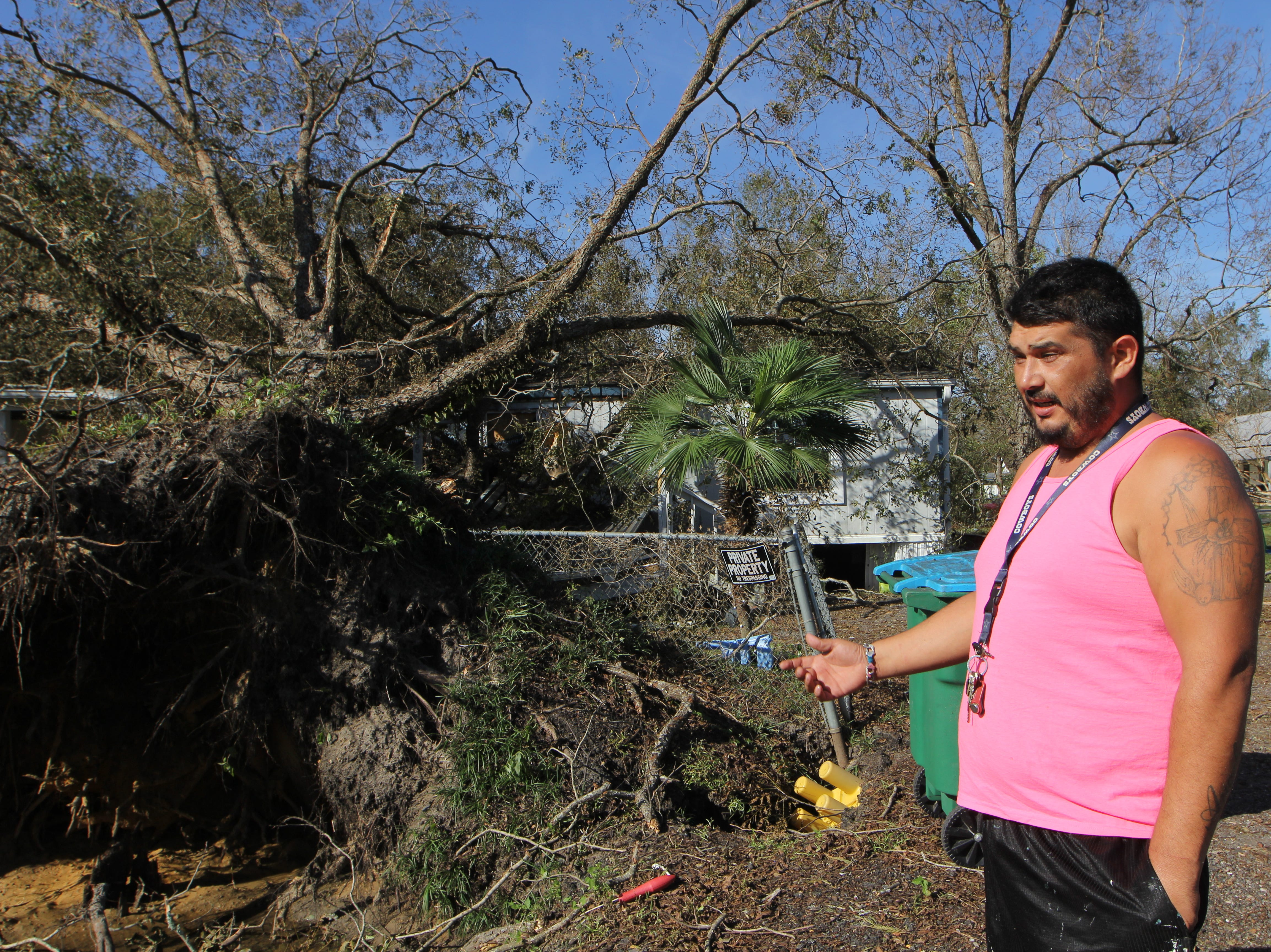 David Garcia, 36, stands on Friday, Oct. 12, 2018, in front of his cousin's home where a large oak tree was uprooted and smashed through the roof in Greensboro in Gadsden County.