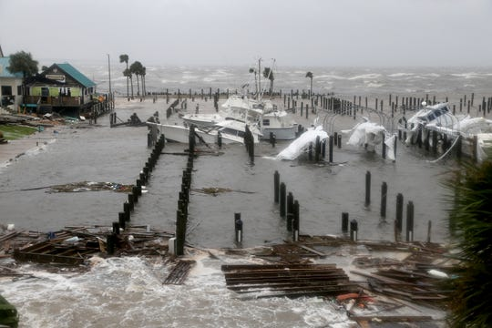 Storm Surge retreats from inland areas, foreground, where boats lay sunk and damaged at the Port St. Joe Marina, Wednesday, Oct. 10, 2018 in Port St. Joe, Fla. Supercharged by abnormally warm waters in the Gulf of Mexico, Hurricane Michael slammed into the Florida Panhandle with terrifying winds of 155 mph Wednesday, splintering homes and submerging neighborhoods. (Douglas R. Clifford/Tampa Bay Times via AP)